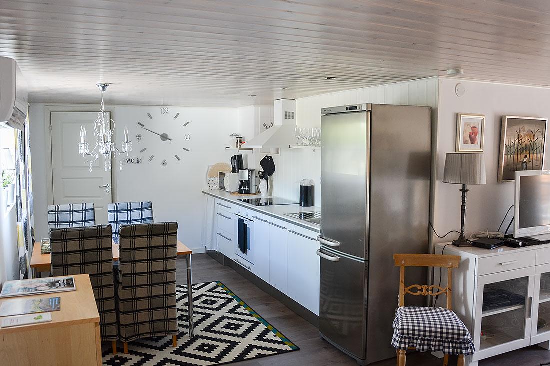 Modernt kök med nödvändigheter som kyl, frys och spis. Även matsalsmöbler för fyra personer