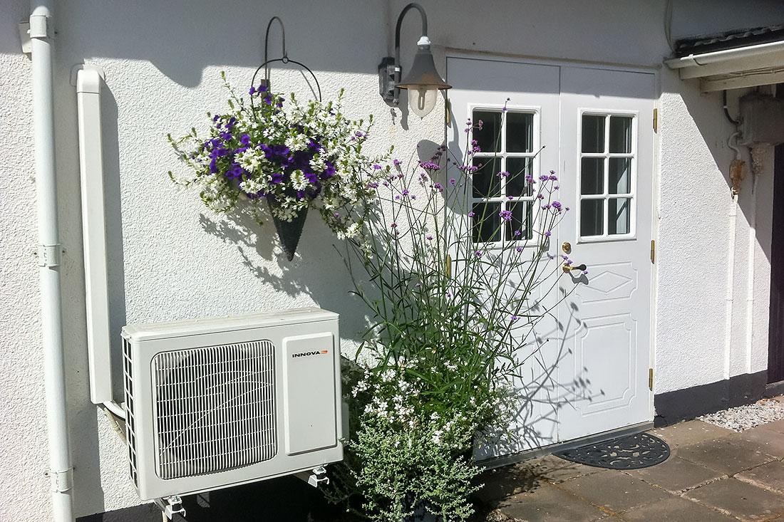 Närbild på entrén till gårdslägenhten. Blommor, utomhusbelysning samt luftkonditionering.